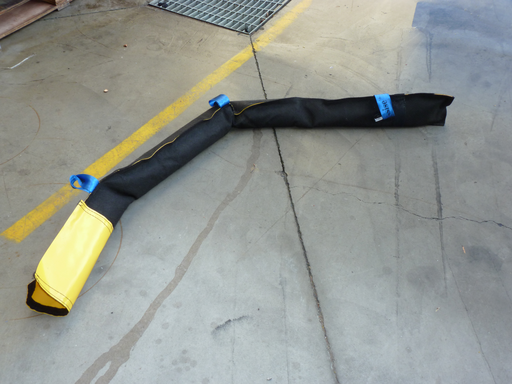weighted containment boom on ground to protect stormwater drain