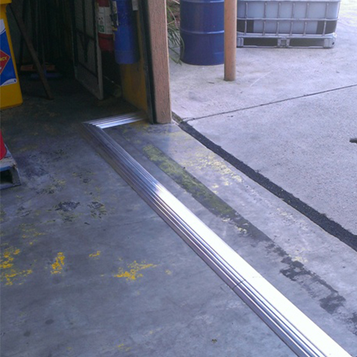aluminium floor bunding installed on a concrete floor at a warehouse drive in entry