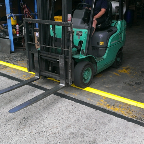 forklift driving over yellow EVA floor bunding installed across a warehouse entry