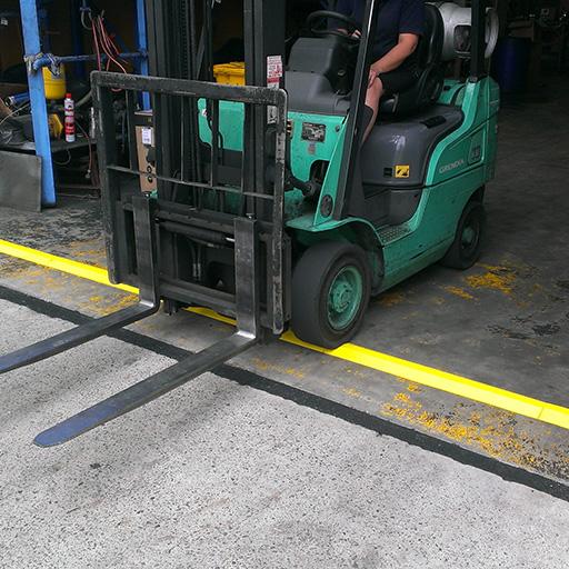 forklift driving over yellow EVA floor bunding installed across a warehouse entry