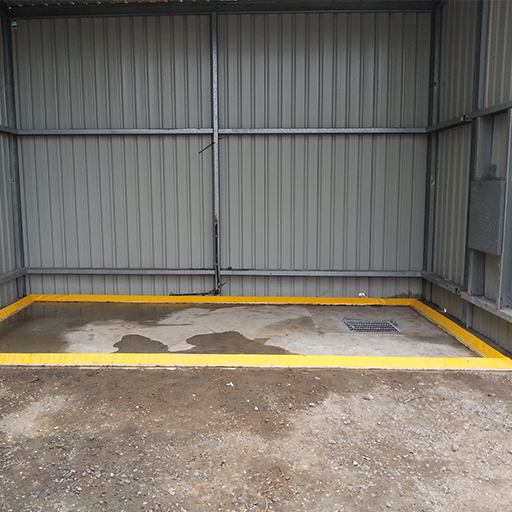yellow flexible floor bunding installed in a squre inside a shed to create a bunded area that will contain used water in a washbay