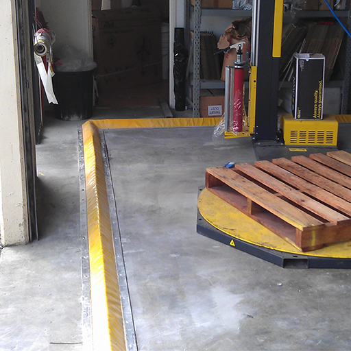 partial view of yellow flexible floor bunding installed on a concrete floor inside a workshop