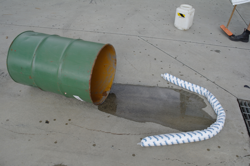 an absorbent mini boom is stopping the spill from a tipped drum from reaching the stormwater drain