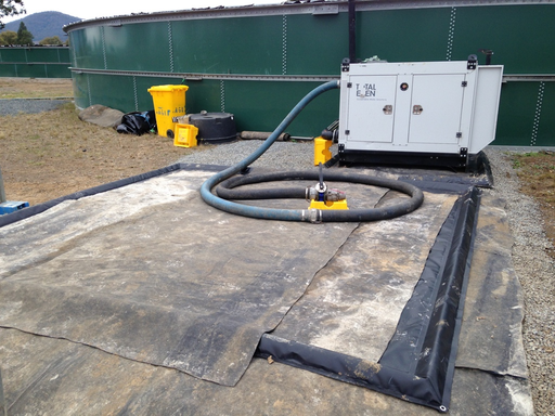 custom spill mat, black geomembrane spill mat used for hose laydown outdoors at a fracking operation
