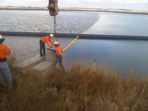 a crew of men are installing anchors on shore for the floating baffles already deployed in the dam