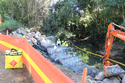 oil containment boom installed during excavation beside a creek