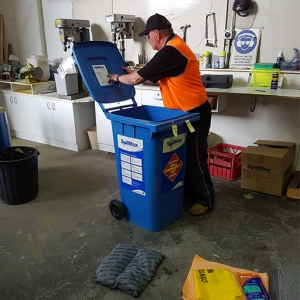 Akuna service man taking inventory of spill kit contents during a spill kit service
