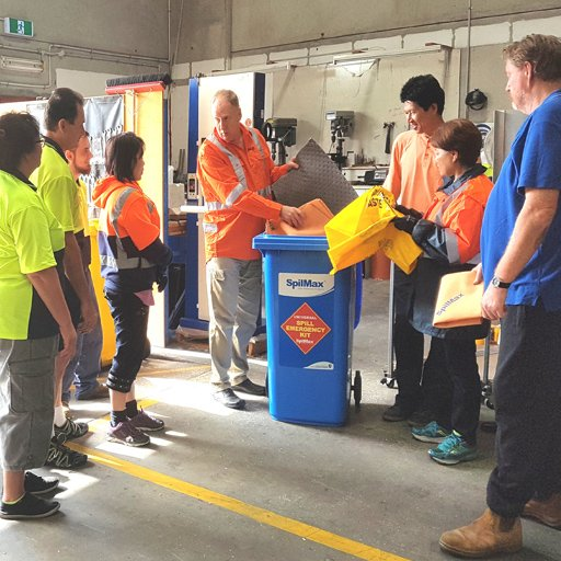 staff at a workplace learning how to use a spill kit in a warehouse during a spill kit tool box talk