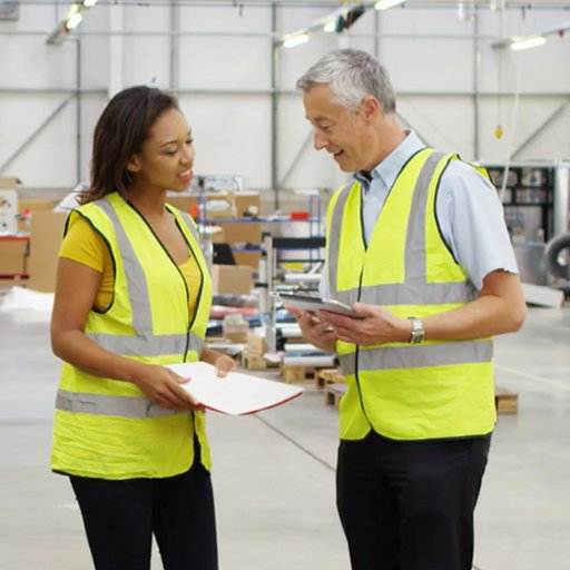 Two people discussing site compliance in a warehouse.